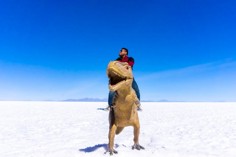 The Man of Wonders riding a T-Rex at the Salar de Uyuni