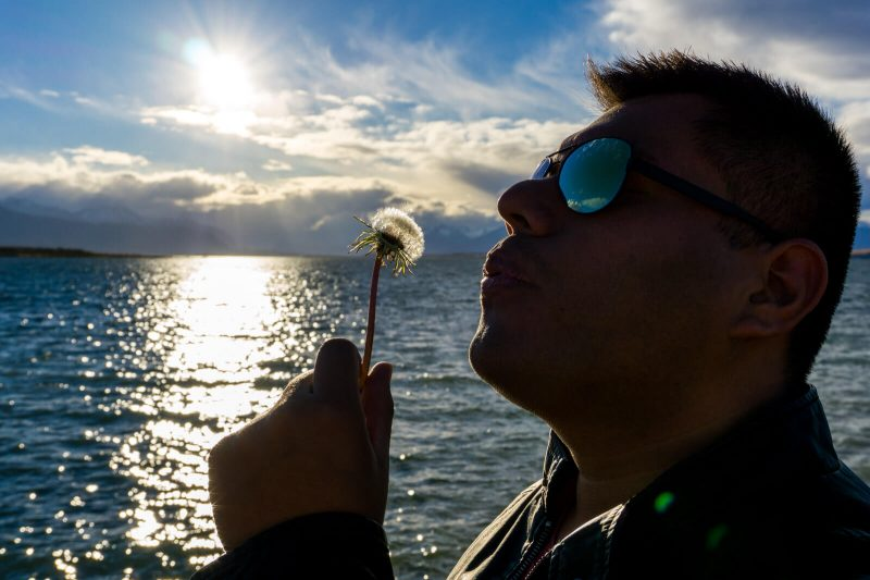 The Man of Wonders blowing a dandelion in Puerto Natales