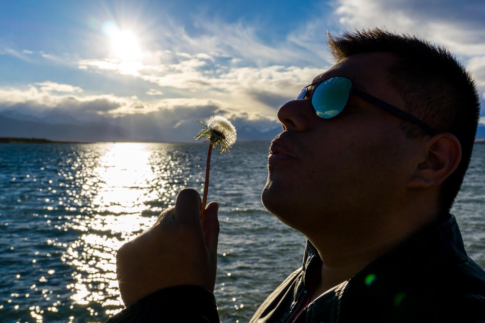 The Man of Wonders blowing a dandelion in Puerto Natales